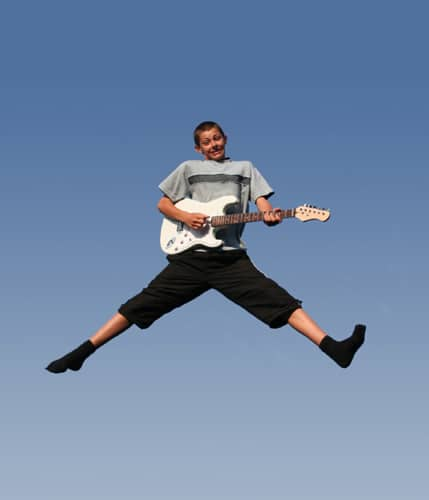 Kid jumping with joy and playing the guitar