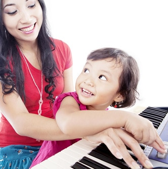 Woman teaching a girl how to play the piano